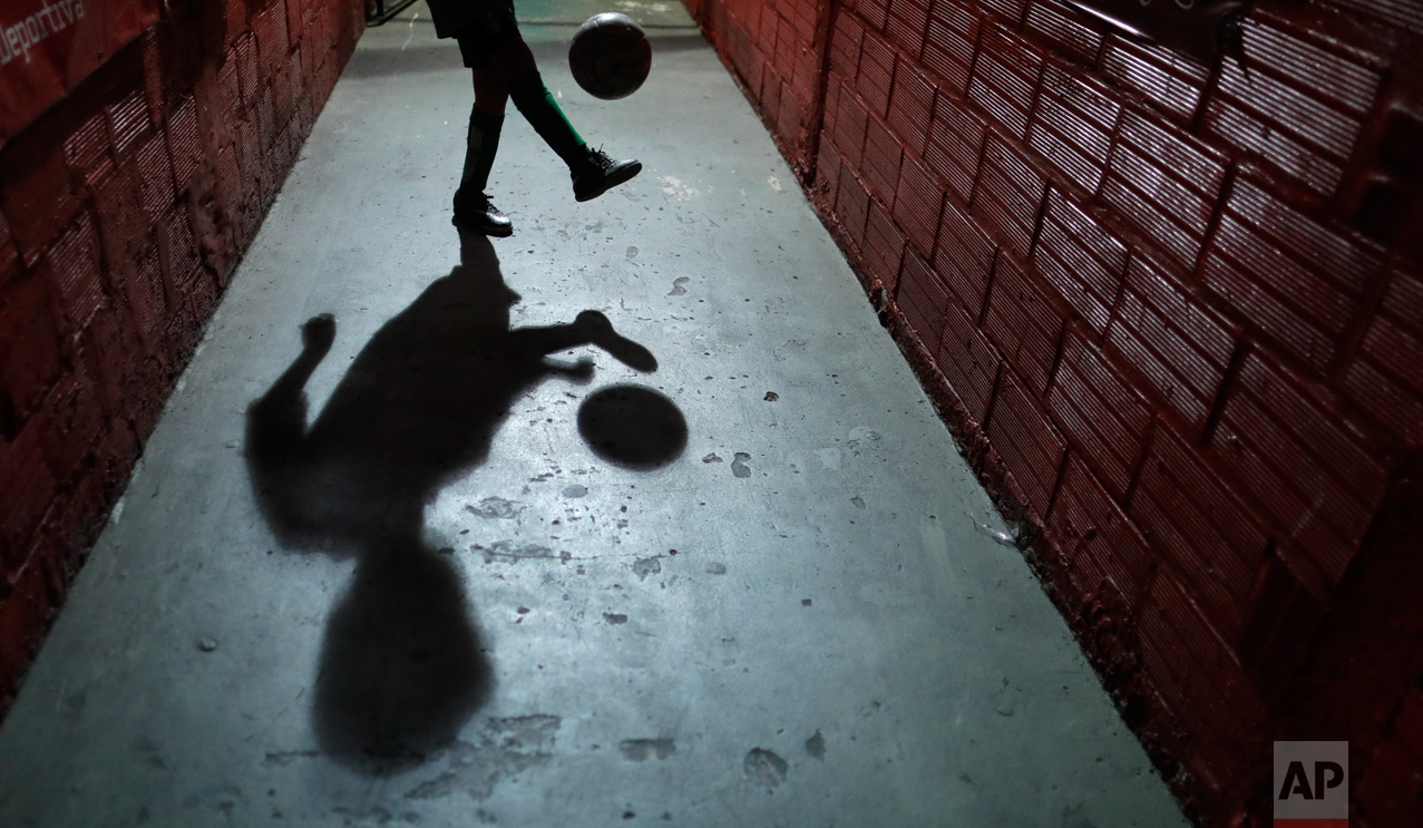 In this Nov. 11, 2016 photo, a child plays with a ball at the youth soccer academy, Club Social Parque, in a working class neighborhood of Buenos Aires, Argentina. Club Social Parque is the same soccer talent factory where international stars like Diego Maradona, Carlos Tevez and Juan Roman Riquelme polished their skills as children. (AP Photo/Natacha Pisarenko)