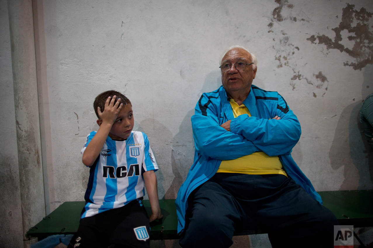 """In this Nov. 11, 2016 photo, head soccer talent scout Ramon Maddoni, of Club Social Parque and Boca Juniors children's division, sits on the bench with young player Benjamin Palandella at the youth soccer academy Club Social Parque in a working class neighborhood of Buenos Aires, Argentina. """"At Club Parque, we work a lot on the fundamentals, the technique. We recognize talent from a young age and our eye has been sharpening with time,"""" said Maddoni. (AP Photo/Natacha Pisarenko)"""