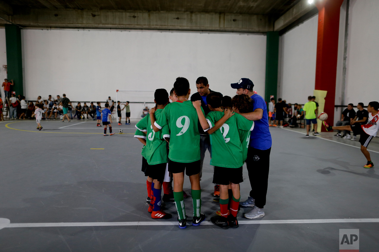 In this March 18, 2017 photo, Club Social Parque players huddle with their coach before a match at the youth soccer academy Club Social Parque in a working class neighborhood of Buenos Aires, Argentina. The humble youth academy has perhaps produced more world-class players than any other. (AP Photo/Natacha Pisarenko)