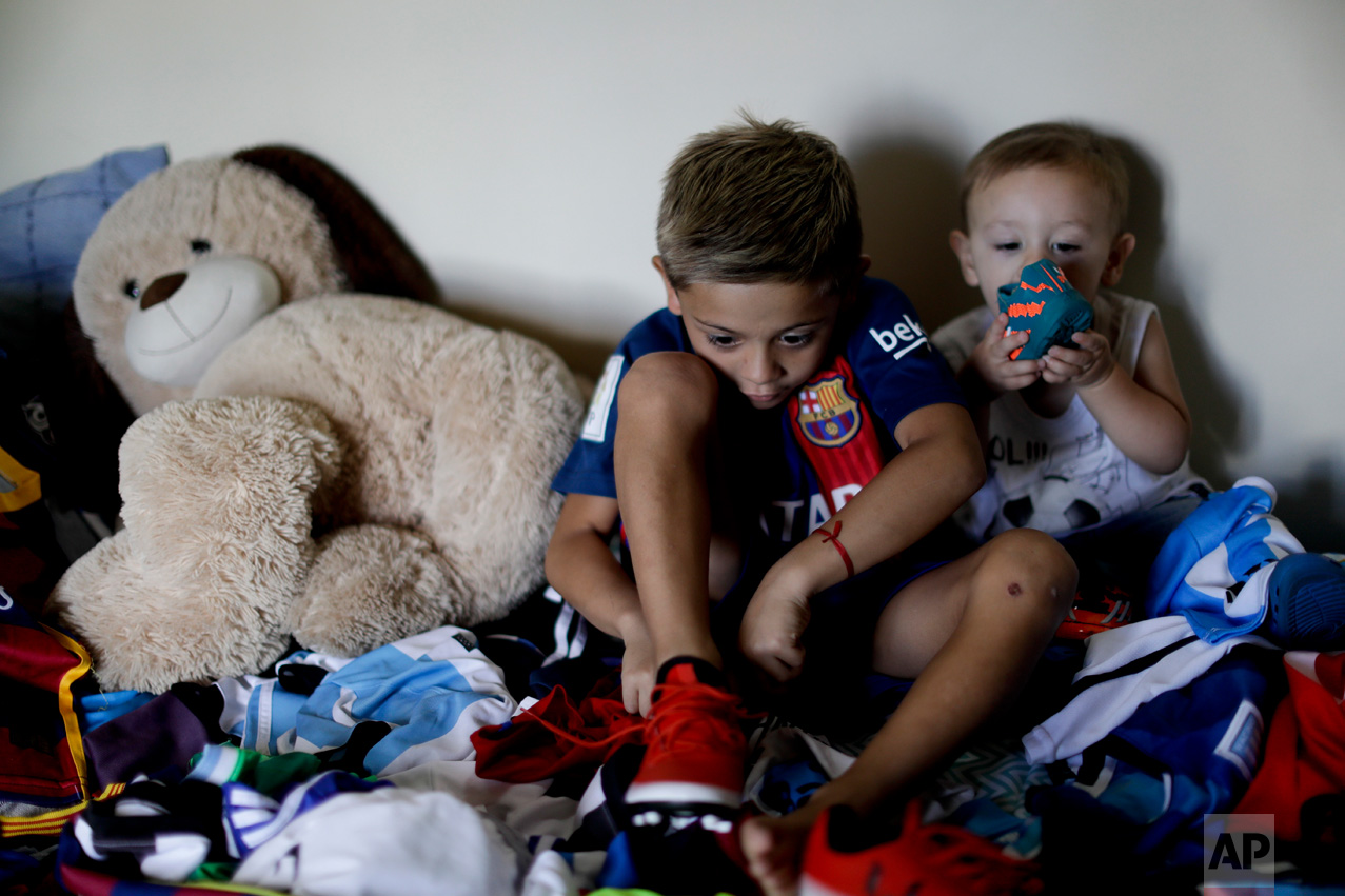 """In this Jan. 25, 2017 photo, Benjamin Palandella puts on his soccer shoes as he sits with his little brother Bautista Lionel and his stuffed toys on his bed in Buenos Aires, Argentina. """"I want to be like Messi and play for Barcelona,"""" said Palandella. He likes how the Barcelona star """"steps"""" on the ball, scores and shoots free kicks. (AP Photo/Natacha Pisarenko)"""