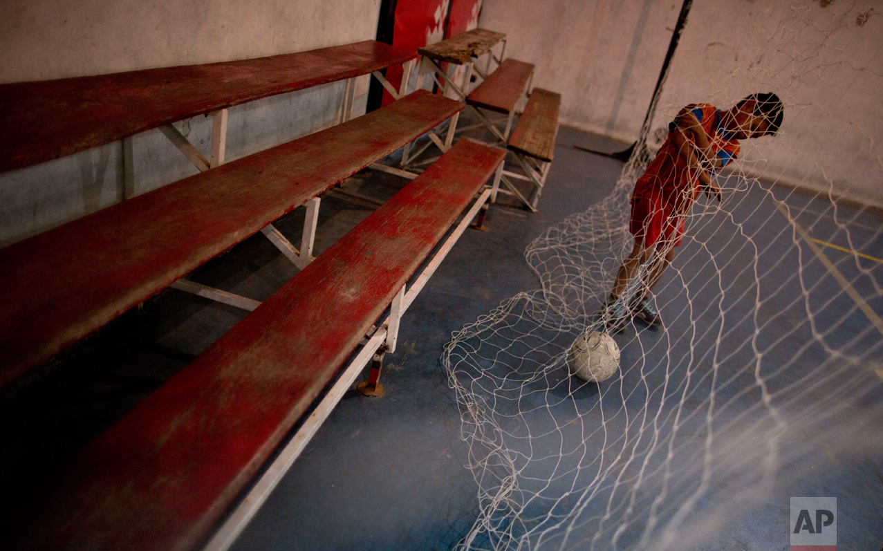 In this Nov. 11, 2016 photo, a young player collects the ball in the net during a training game at youth soccer academy Club Social Parque in a working class neighborhood of Buenos Aires, Argentina. Former players say the secret to Parque is the eye of scout Ramon Maddoni for spotting young talent and his insistence on practicing skill sets in reduced spaces and imperfect surfaces where kids learn how to react faster, giving them a competitive advantage when they eventually reach large professional fields. (AP Photo/Natacha Pisarenko)