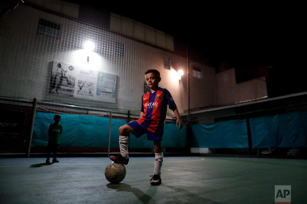 """In this Nov. 11, 2016 photo, Benjamin Palandella poses for a portrait wearing his Barcelona shirt after a training session in Buenos Aires, Argentina. Palandella's coach Ramon Maddoni said """"Benjamin is different from the group. He can pass with his back turned, he uses both legs."""" (AP Photo/Natacha Pisarenko)"""