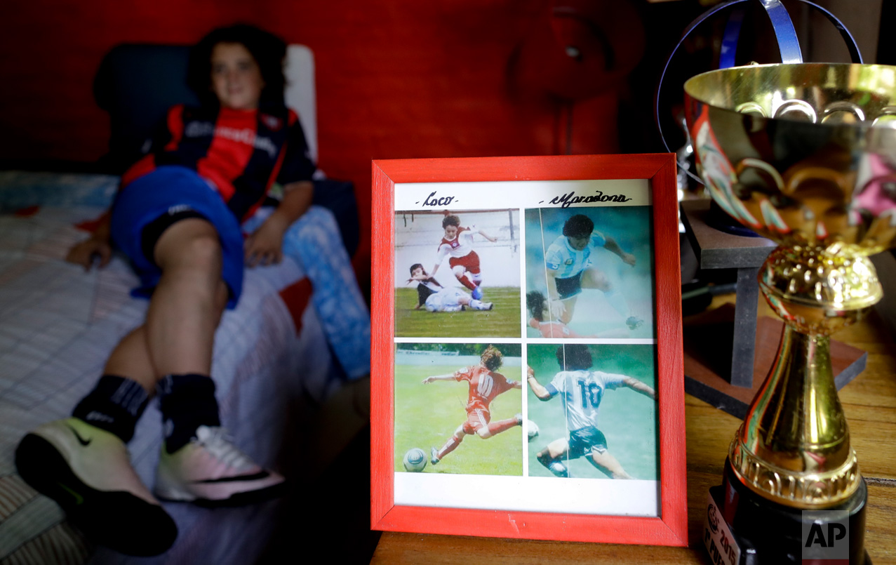 """In this Nov. 19, 2016 photo, a framed picture shows Thiago """"Coco"""" Perugini next to images of soccer star Diego Maradona, at his home where he lies on bed, on the outskirts of Buenos Aires, Argentina. Like Maradona, Thiago is a classic playmaker. He knows that he wants to be a professional soccer player. But what would he do, if he doesn't end up going pro? After a long silence, he shrugs his shoulders, smiles and answers: """"I don't know."""" (AP Photo/Natacha Pisarenko)"""