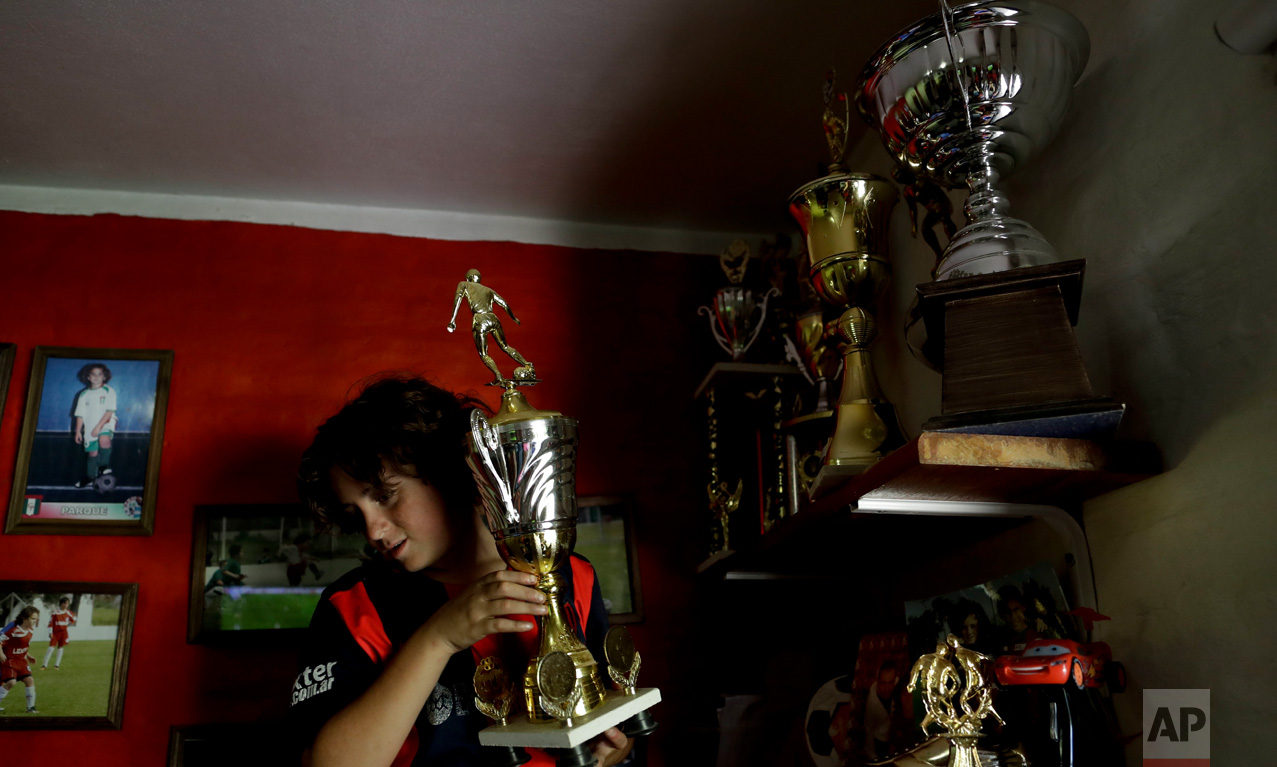 """In this Nov. 19, 2016 photo, Thiago """"Coco"""" Perugini shows one of his trophies to journalists inside his room on the outskirts of Buenos Aires, Argentina. Thiago recently transferred to the youth division of San Lorenzo and his parents had his wall painted in the club's red and blue colors. (AP Photo/Natacha Pisarenko)"""