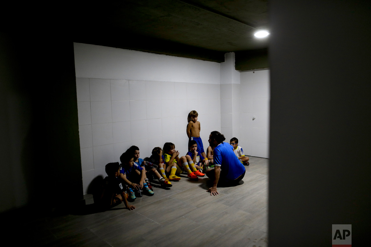 In this March 18, 2017 photo, coach Ariel Picallo talks to his team of 7-year-olds after they lost a game at the youth soccer academy Club Social Parque in a working class neighborhood of Buenos Aires, Argentina. At his youth soccer academy, about 150 children as young as 6 from all economic levels train together twice a week and compete on the weekends. (AP Photo/Natacha Pisarenko)