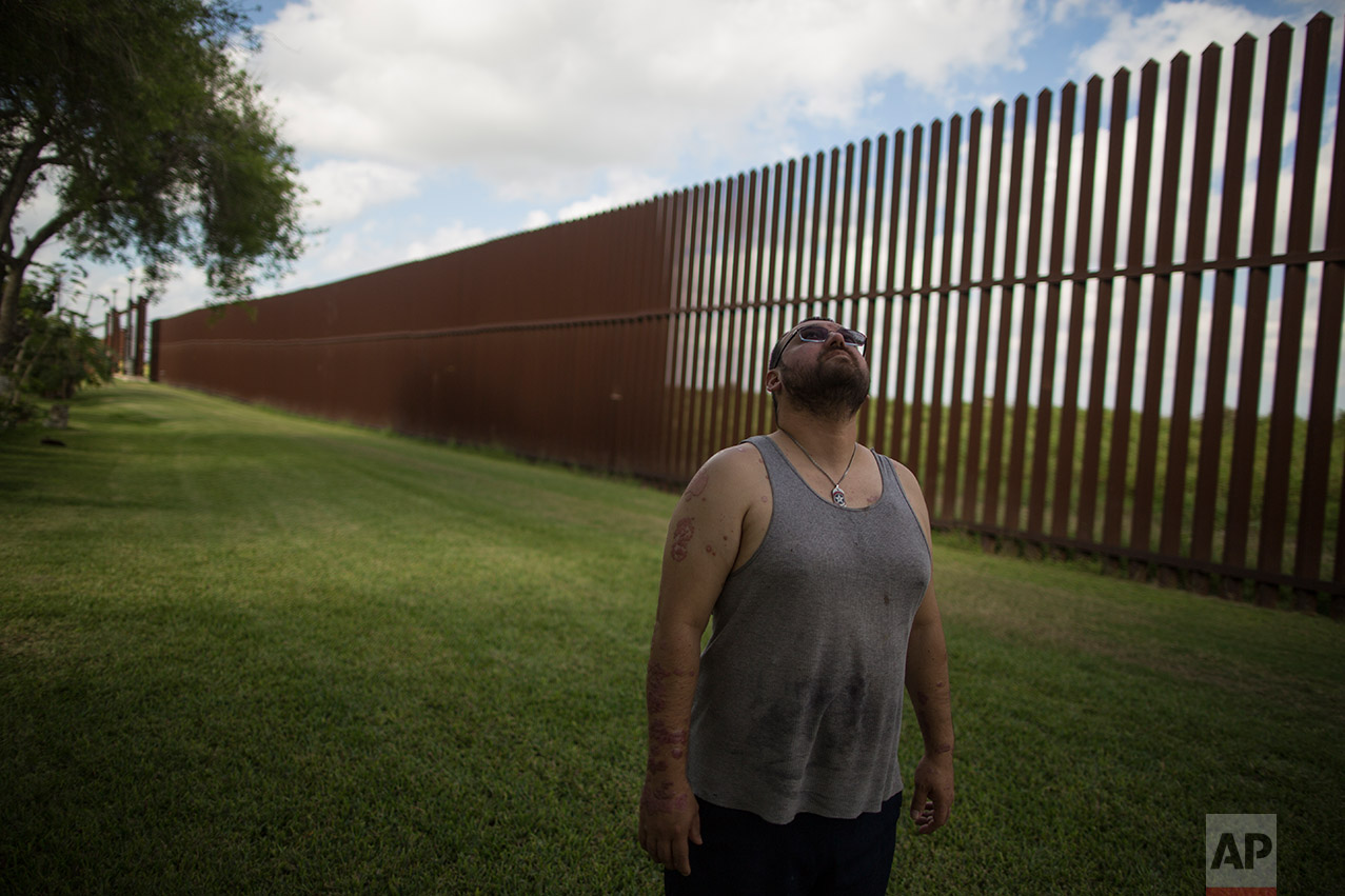U.S. citizen Antonio Reyes stands by the U.S.-Mexico border fence where his home's located in Brownsville, Texas, Wednesday, March 22, 2017. (AP Photo/Rodrigo Abd)