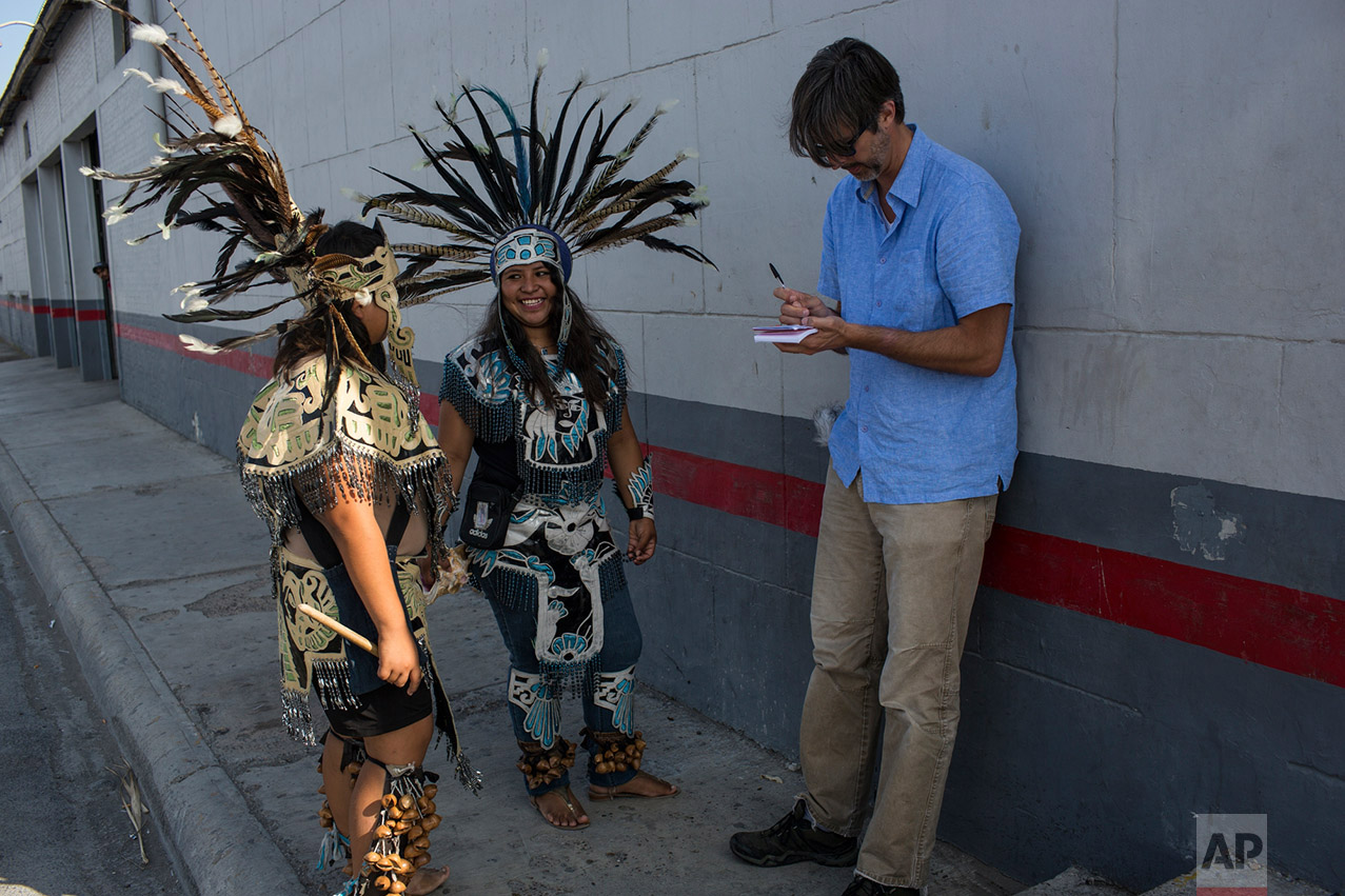Performers form Oaxaca, Sarahi Manzano, 16, center, smiles next to her brother Juan Manzano, 13, while talking to The Associated Press reporter Cris Sherman, Reynosa, Tamaulipas, Mexico, Wednesday, Thursday, 23, 2017. (AP Photo/Rodrigo Abd)