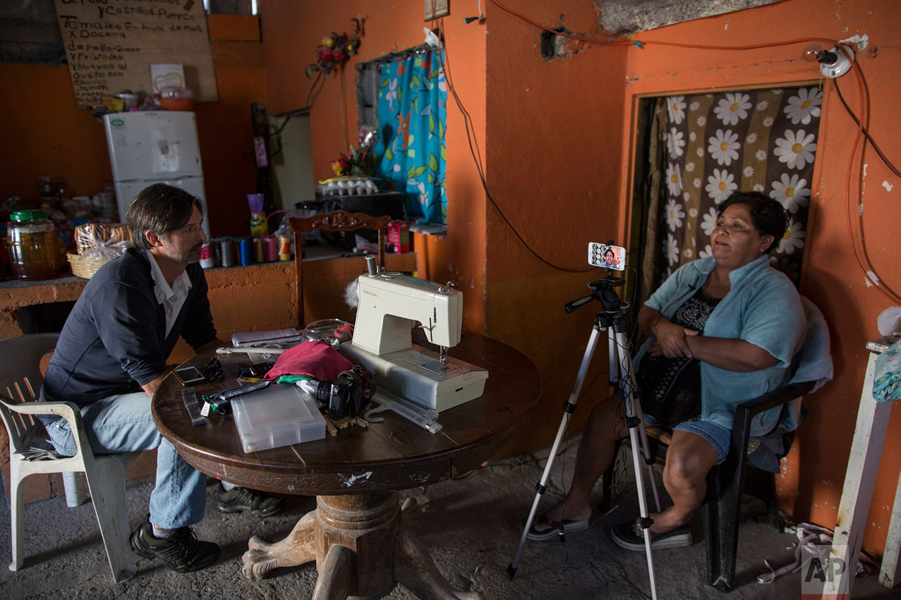Reporter Cris Sherman during an interview with Jesus Esteban Cruz, stands inside her bedroom in Reynosa, Mexico, Wednesday, March, 22, 2017. (AP Photo/Rodrigo Abd)
