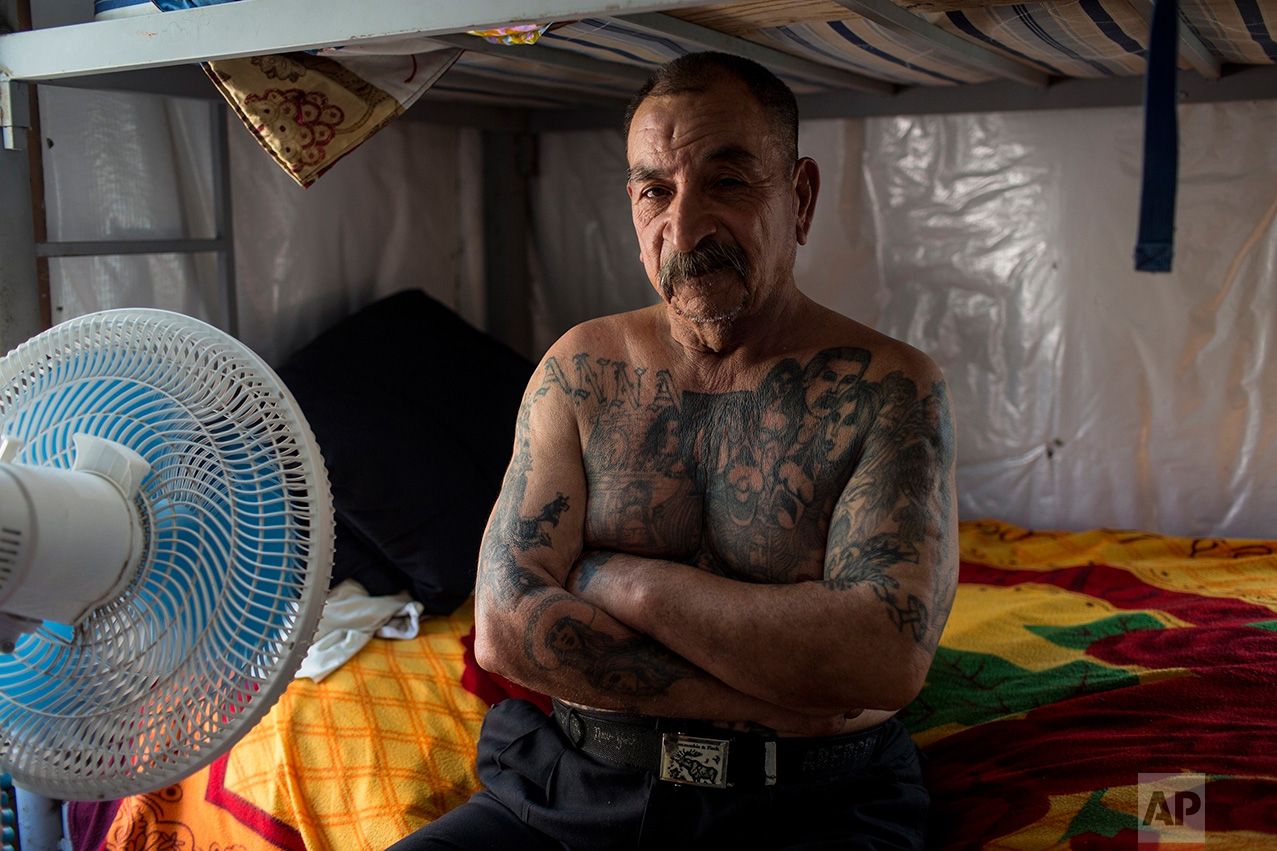 """Mexican migrant Juan Parras, 65, covered in tattoos, poses for a portrait in the dormitory at the migrant shelter """"Senda de Vida"""" in Reynosa, Mexico, Wednesday, March 22, 2017. Parras said he was deported one year ago from California, where he left behind three sons, and he plans to try to return but it's more difficult now to get past U.S. security. Regarding the proposed border wall, Parras said """"Mexico is not going to pay for the wall."""" (AP Photo/Rodrigo Abd)"""