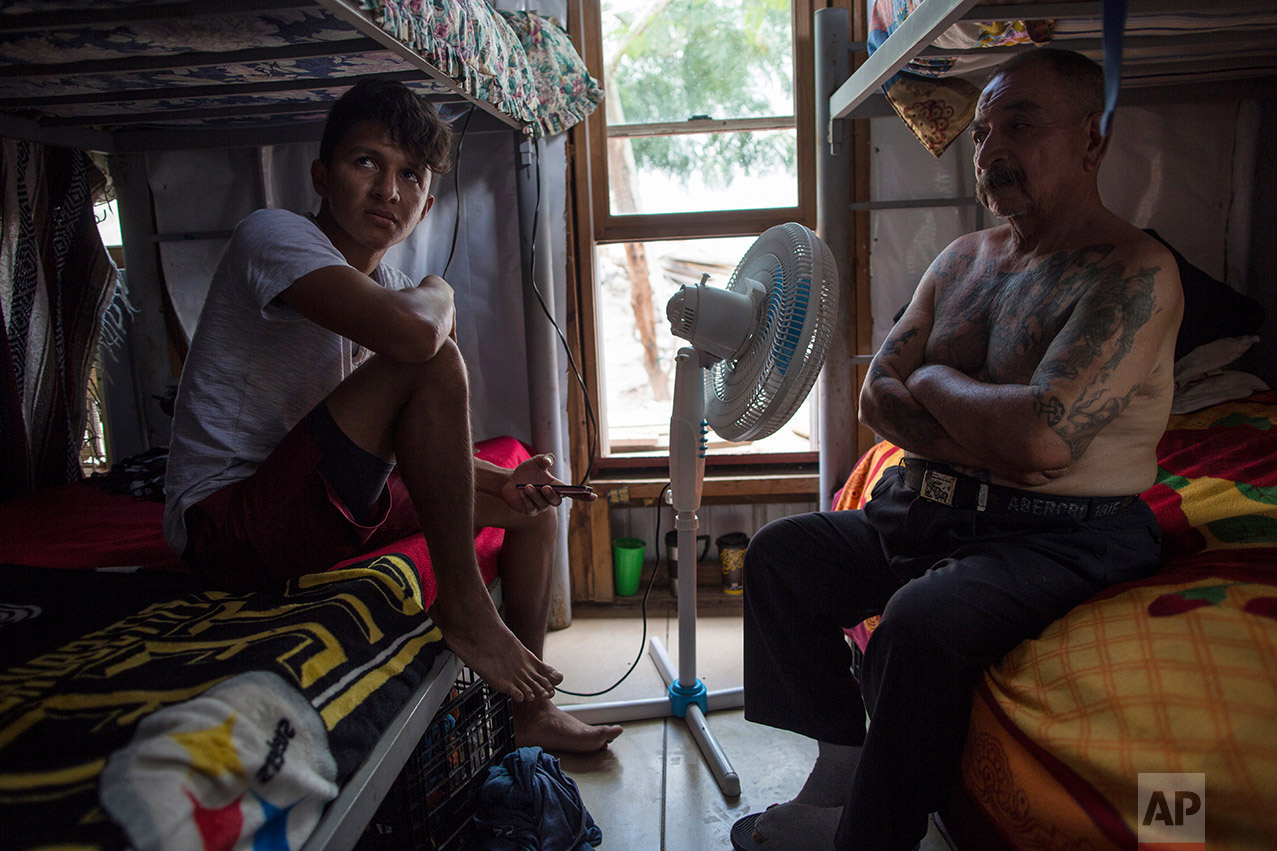 """Migrants Juan Parras, 65, right, and Junior Matute, 19, rest on their beds at the migrant shelter """"Senda de Vida"""" in Reynosa, Mexico, Wednesday, March, 22, 2017. Matute said his brother was deported from the United States to Honduras and then murdered in February 2016. """"I come for a reason. It's not like one day I just decided to leave my country,"""" he says. Parras said he was deported one year ago from California, where he left behind three sons, and that he plans to try to return. (AP Photo/Rodrigo Abd)"""