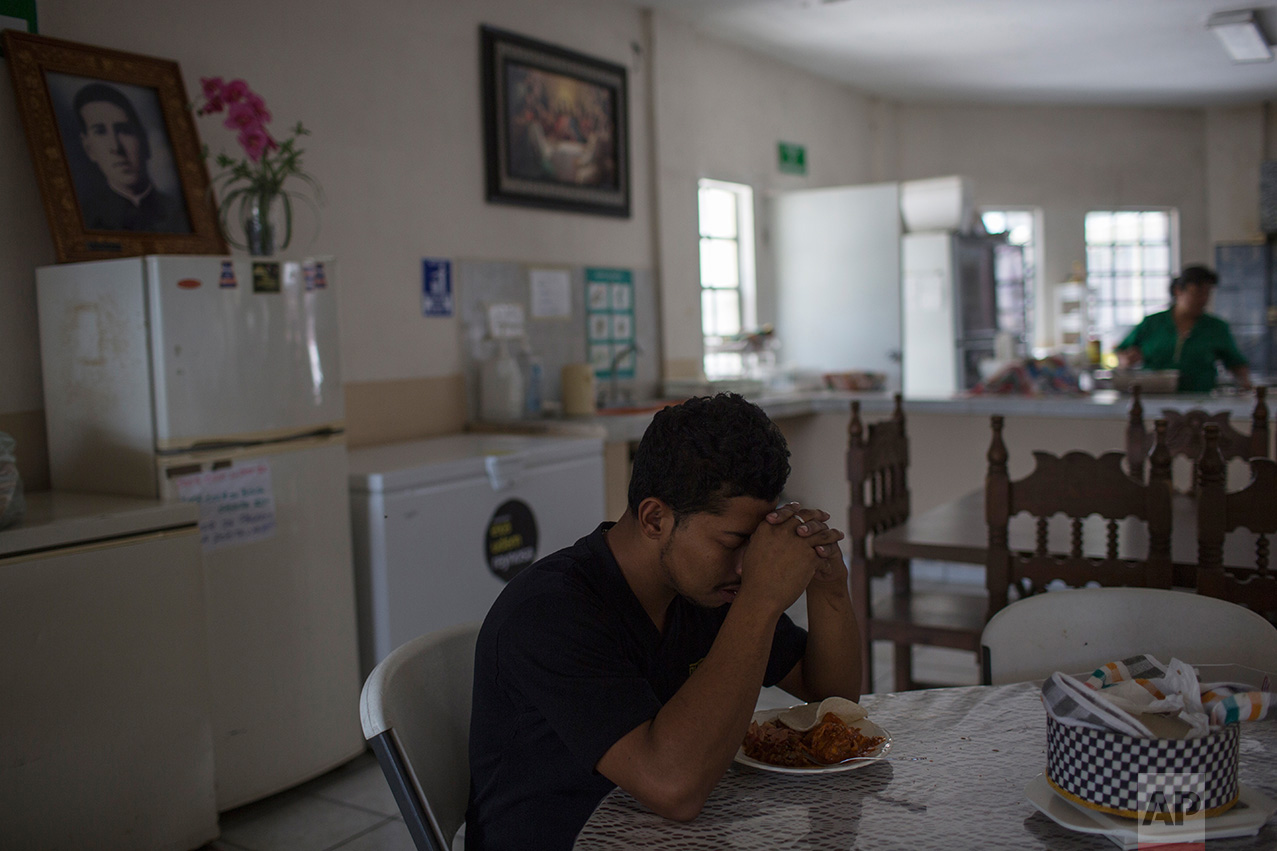 "A deported migrant prays before eating lunch in ""La Casa del Migrante"" migrant shelter in Reynosa, Mexico, Wednesday, March 22, 2017. (AP Photo/Rodrigo Abd)"