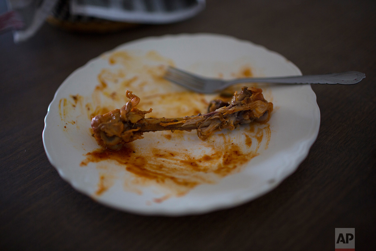 """A bare chicken bone lays on a lunch plate after a meal at the migrant shelter """"La Casa del Migrante"""" in Reynosa, Mexico, Wednesday, March, 22, 2017. (AP Photo/Rodrigo Abd)"""