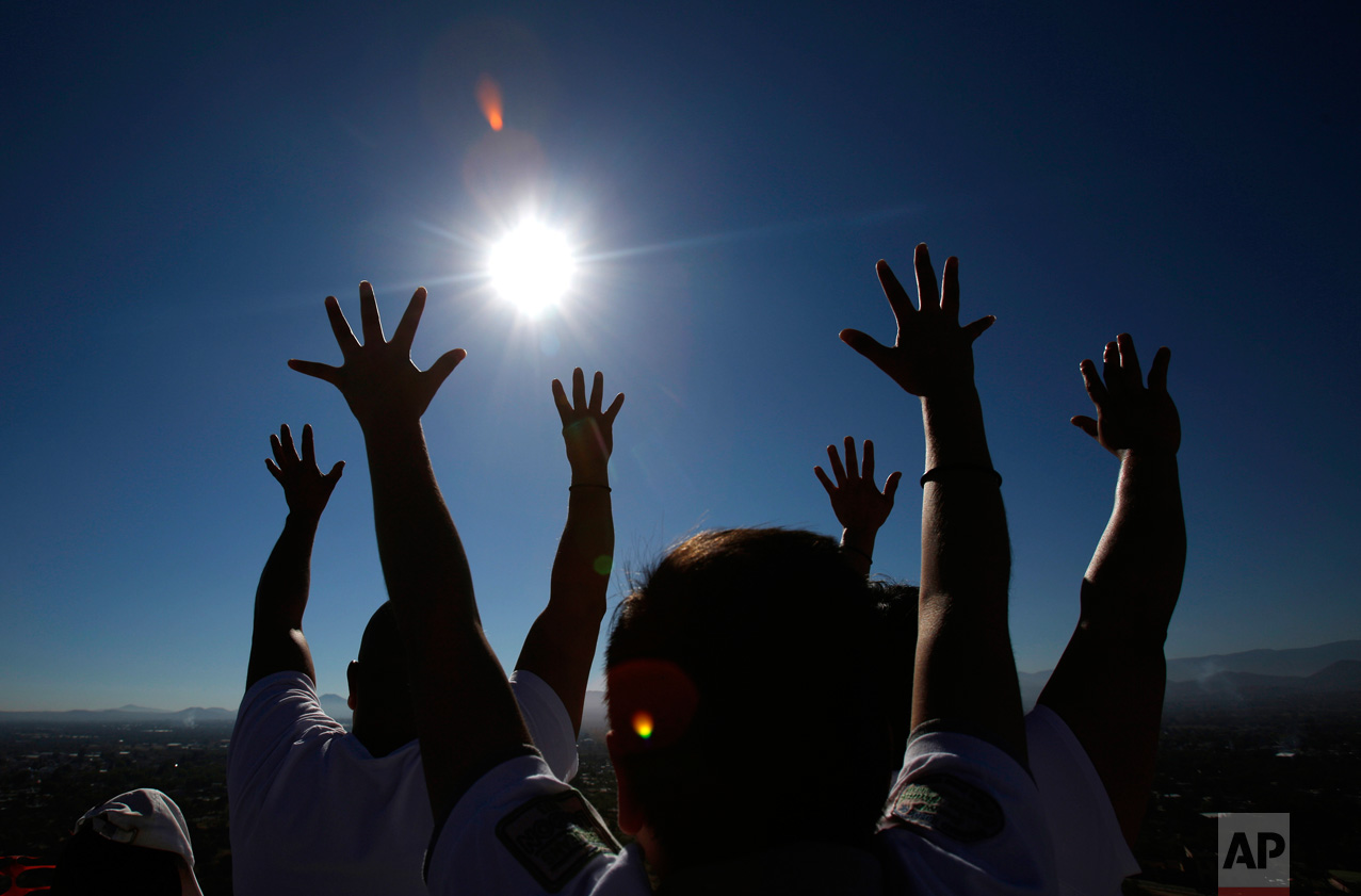 Family members celebrating the spring equinox raise their hands toward the sun atop the Pyramid of the Sun at the Teotihuacan archeological site in Mexico, on Tuesday, March 21, 2017 Although the official vernal equinox occurred on Monday, thousands of visitors were expected to climb the ancient pyramid on Tuesday to greet the sun and celebrate the beginning of spring. (AP Photo/Rebecca Blackwell)
