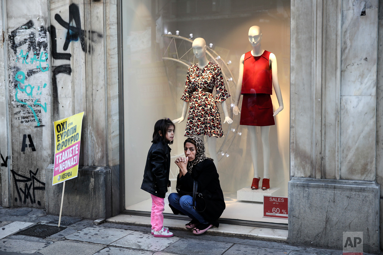 """A refugee and her daughter sit next to a placard in front of a shop window during a rally in Athens, Saturday, March 18, 2017. Thousands of protesters marched to the offices of the European Commission Representation in Greece to mark the United Nations' Anti-Racism Day. The placard reads: """"No to a fortress-Europe, Crush the Neo-Nazis"""". (AP Photo/Yorgos Karahalis)"""