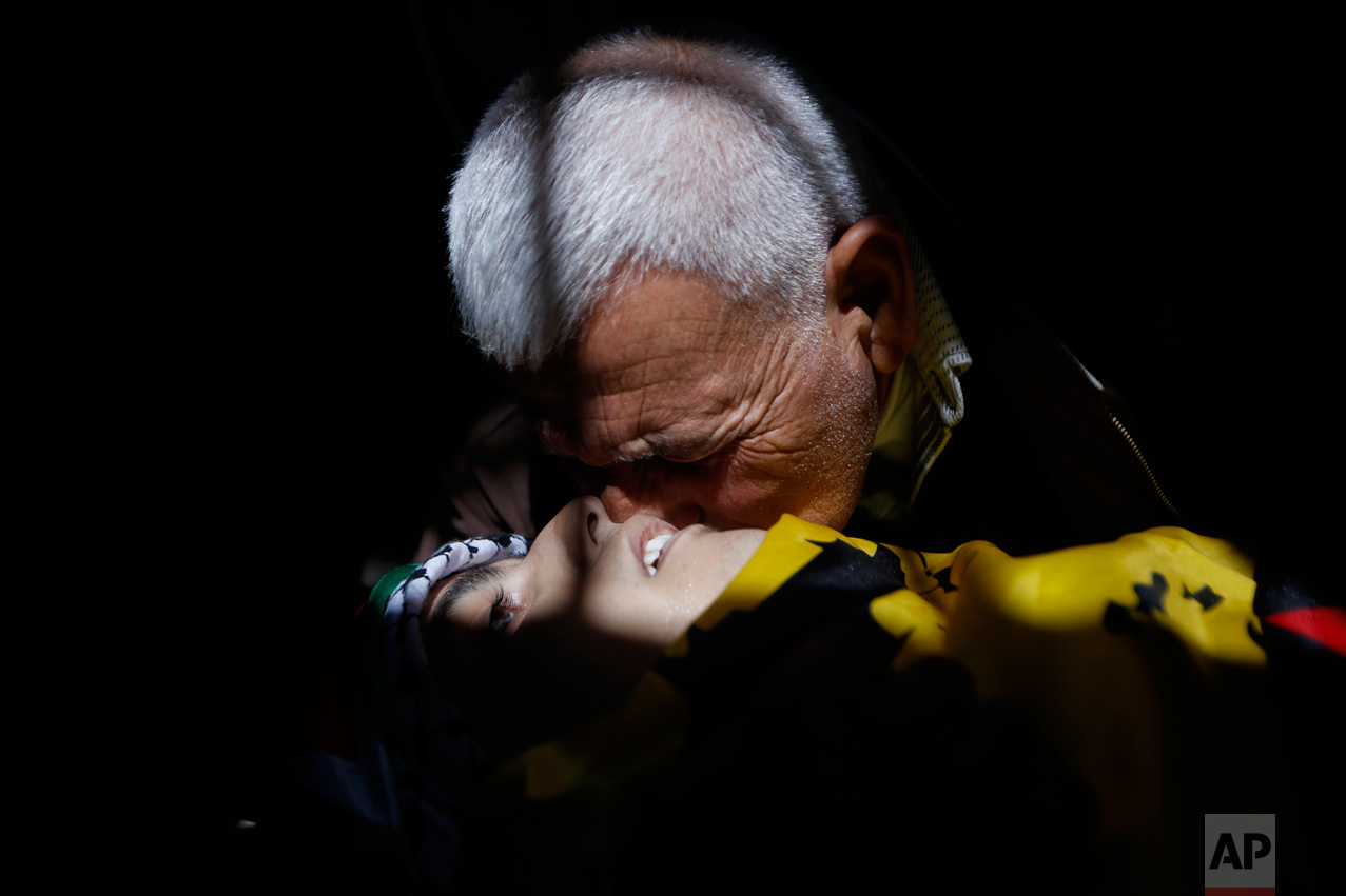 """A relative kisses the cheek of 17-year old Palestinian Mahmoud Hattab during his funeral at the Jalazoun refugee camp near the West Bank city of Ramallah, Friday, March 24, 2017. The Palestinian Health Ministry said Israeli troops killed the teenager and wounded another three when soldiers opened fire on their vehicle in the West Bank. The Israeli military said the men had stopped near a Jewish settlement and """"hurled fire bombs"""" at the community, and the soldiers fired at the attackers who fled the scene in their vehicle. (AP Photo/Majdi Mohammed)"""