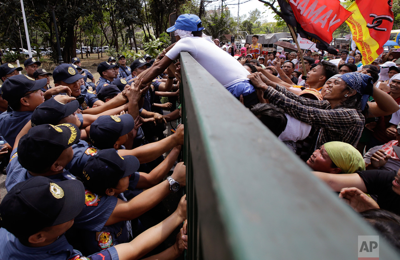 """Police officers stop a demonstrator from trying to open the gates of the National Housing Authority offices during a rally in Quezon City, Philippines, northeast of Manila, on Friday, March 24, 2017. The group is protesting the possible eviction to hundreds of informal settlers who have occupied a housing community for police and military in northern province of Bulacan. In a statement, the occupants deemed the eviction notice a """"violation of urban poor rights"""" and vowed to resist any move to evict them. (AP Photo/Aaron Favila)"""