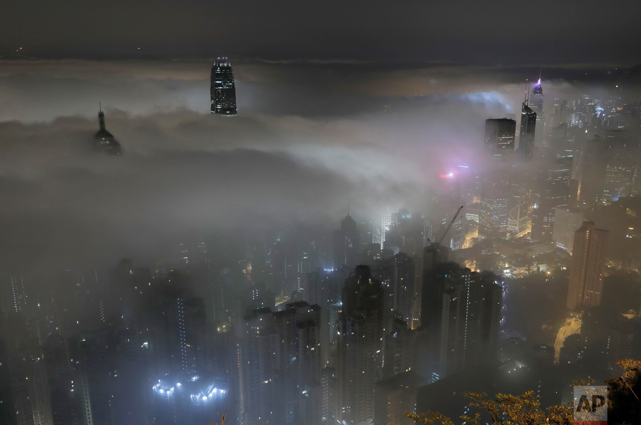 High-rise buildings are partly covered by heavy fog in Hong Kong's Victoria Harbour on Monday, March 20, 2017. Fog blanketing the city is common in spring and can greatly affect shipping and aviation. (AP Photo/Vincent Yu)