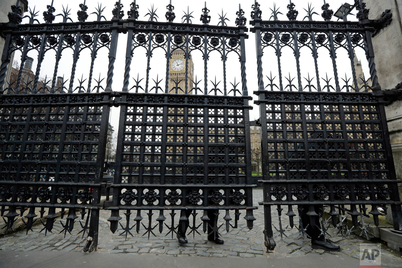Police officers adjust a panel on a gate outside the Houses of Parliament in London, Friday, March 24, 2017. On Thursday authorities identified a 52-year-old Briton as the man who mowed down pedestrians and stabbed a policeman to death outside Parliament, saying he had a long criminal record and once was investigated for extremism — but was not currently on a terrorism watch list. (AP Photo/Matt Dunham)
