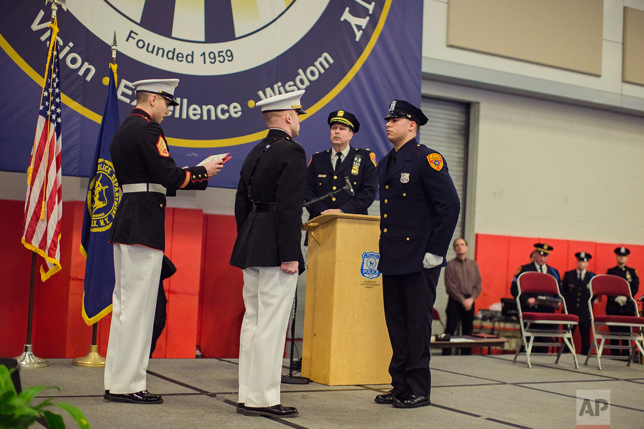 Matias Ferreira, center, receives his diploma during his graduation from the Suffolk County Police Department Academy at the Health, Sports and Education Center in Suffolk, Long Island, New York, Friday, March 24, 2017. (AP Photo/Andres Kudacki)