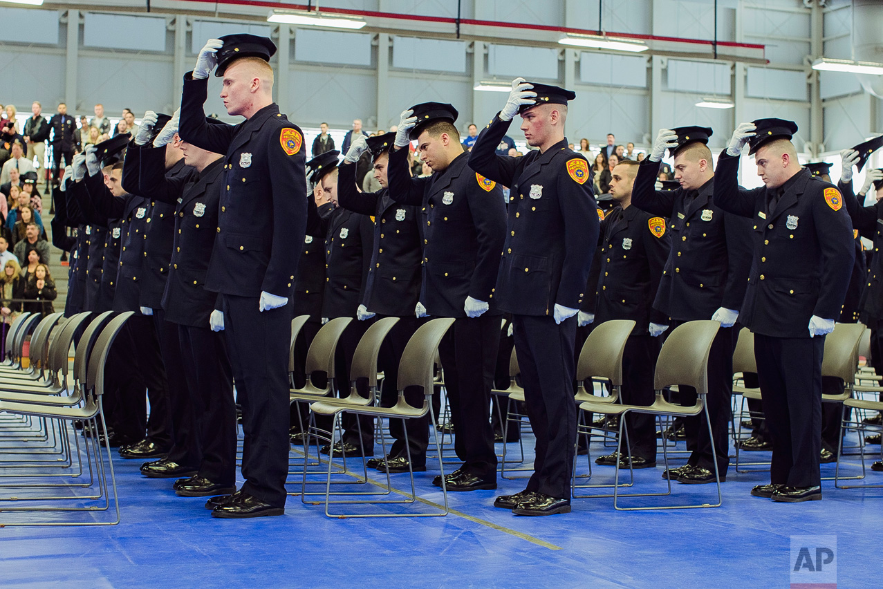 Matias Ferreira, second row, second, and his colleagues take off his hat during their graduation from the Suffolk County Police Department Academy at the Health, Sports and Education Center in Suffolk, N.Y., Friday, March 24, 2017. (AP Photo/Andres Kudacki)
