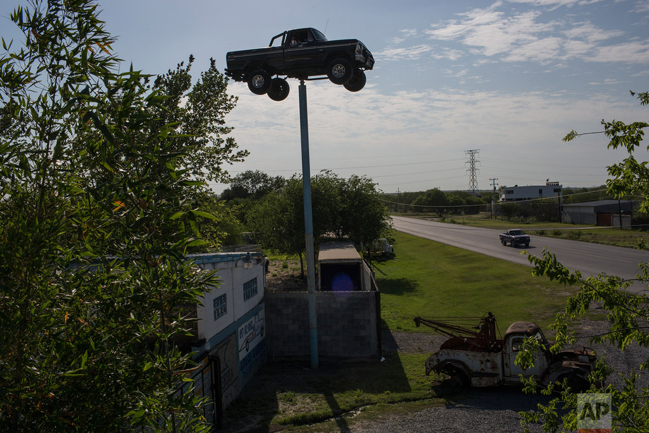 A truck advertising an auto body repair shop is seen behind the cemetery in Los Guerra, Tamaulipas, Mexico, Wednesday, Thursday, 23, 2017. (AP Photo/Rodrigo Abd)