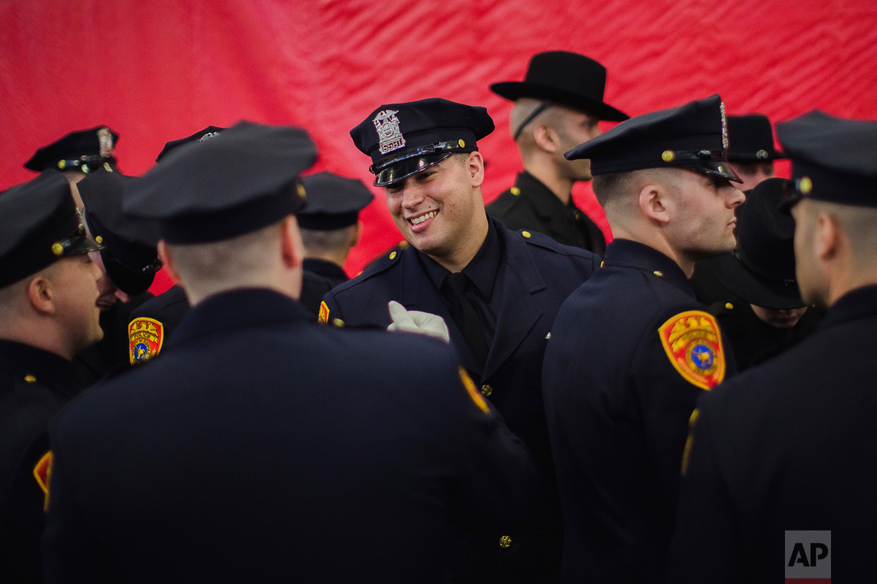 Matias Ferreira, center, celebrates with his colleagues during their graduation from the Suffolk County Police Department Academy at the Health, Sports and Education Center in Suffolk, N.Y., Friday, March 24, 2017. (AP Photo/Andres Kudacki)