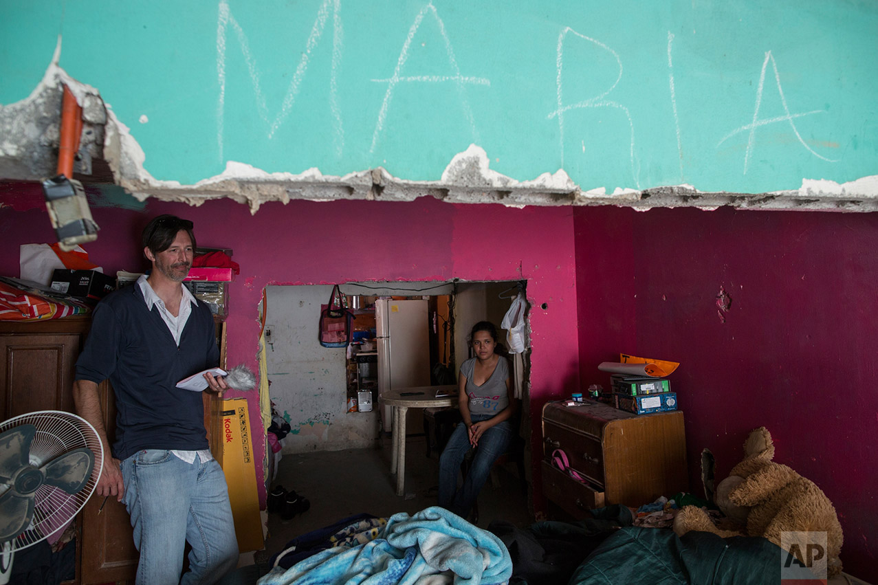 AP journalist Christopher Sherman interviews Maria Paula Esteban Cruz, right, and her mother, Jesus Esteban Cruz (not in the picture), inside their home in Reynosa, Mexico, Wednesday, March 22, 2017, across the border from McAllen, Texas. (AP Photo/Rodrigo Abd)