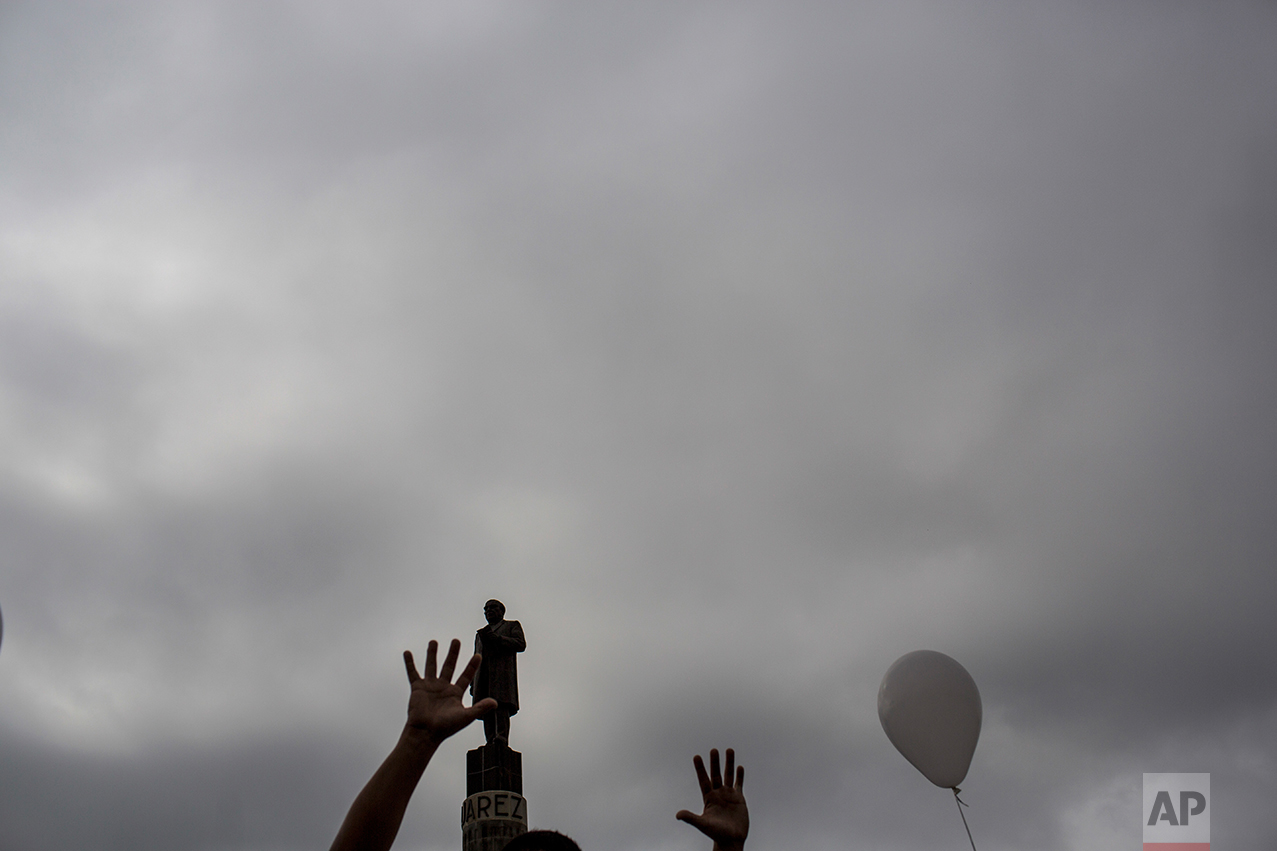 A man gestures while passing next to a statue former Mexico's President Benito Juarez during a march against violence organized by local churches in Nuevo Laredo, Tamaulipas state, Mexico, Saturday March, 25, 2017. (AP Photo/Rodrigo Abd)