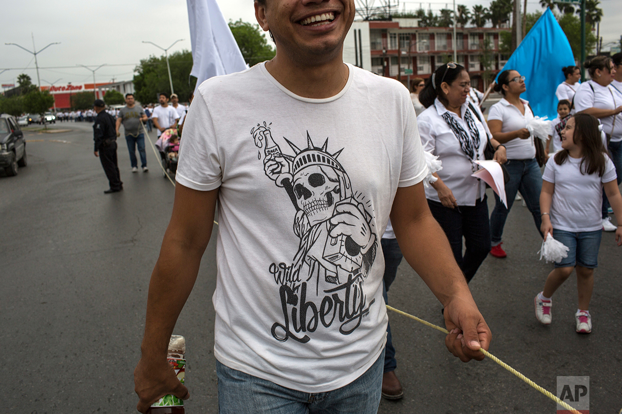 A man wearing a T-shirt depicting the statue of liberty with a skull face laughs as he walks during a march against violence organized by local churches in Nuevo Laredo, Tamaulipas state, Mexico, Saturday March, 25, 2017. (AP Photo/Rodrigo Abd)