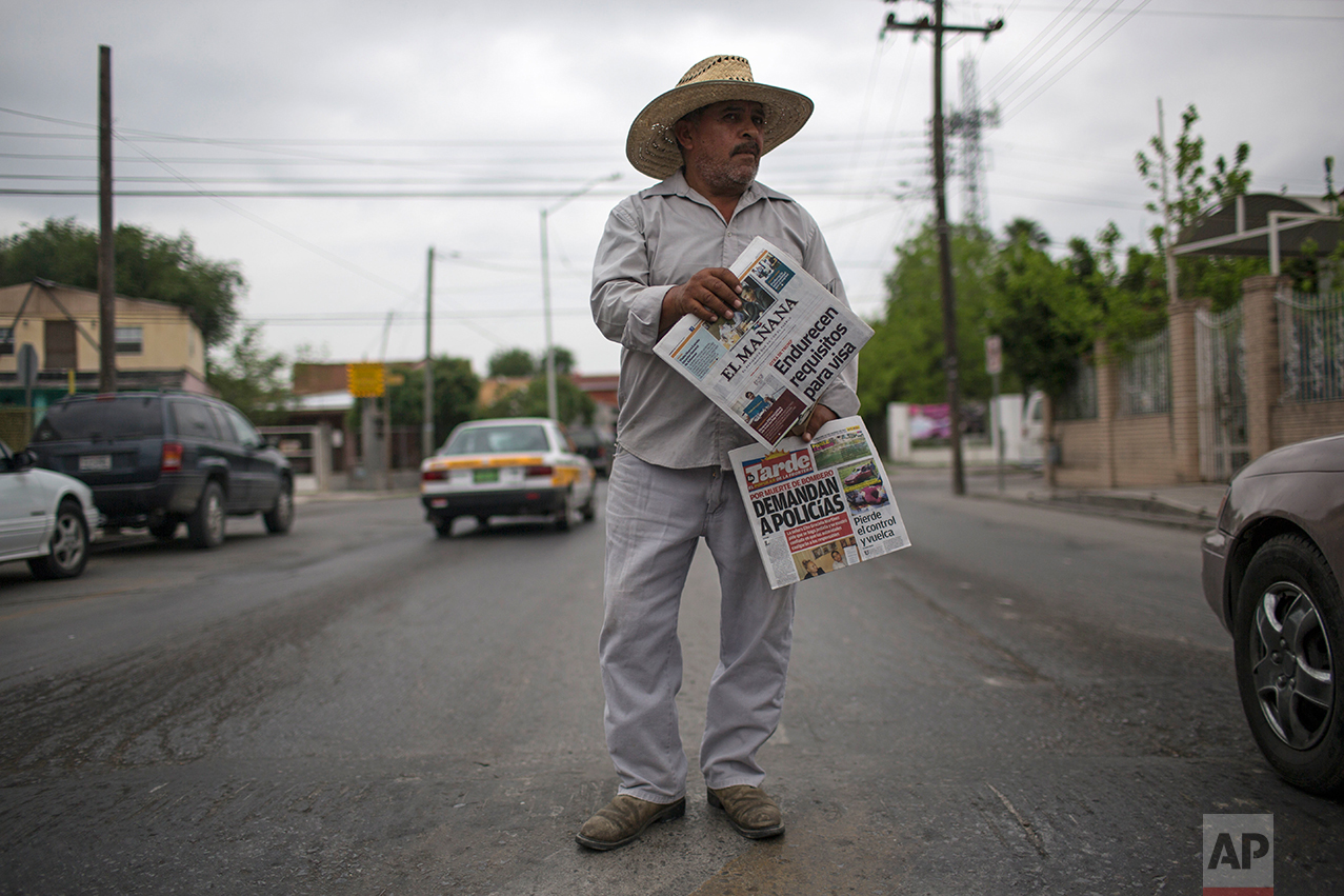 A man sells newspapers in downtown Nuevo Laredo, Tamaulipas state, Mexico, across the border from Laredo in the U.S, Friday March 24, 2017. Th headlines read in Spanish 'visa requirements get harder' top, and 'policemen are sued', bottom.(AP Photo/Rodrigo Abd)