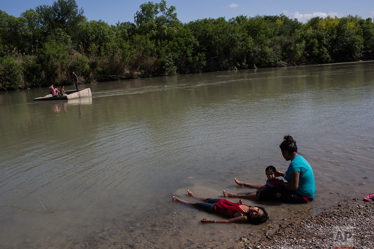 People cool off in the Rio Grand river, or Rio Grande and Rio Bravo in Spanish, in Nuevo Laredo, Tamaulipas state, Mexico, Saturday, March 25, 2017, across the border from Laredo, Texas. (AP Photo/Rodrigo Abd)