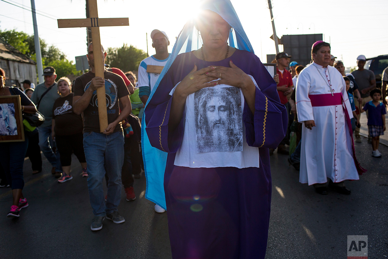 Cuban Idenia Vidal leads a religious procession adapted to reflect the plight of immigrants, in Nuevo Laredo, Tamaulipas state, Mexico, Friday, March, 24, 2017, across the border from Laredo, Texas. (AP Photo/Rodrigo Abd)