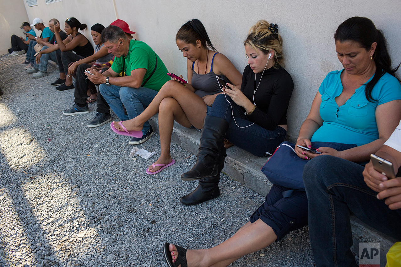"Cubans check their cell phones inside the migrant shelter ""Casa del Migrante"" in Nuevo Laredo, Tamaulipas state, Mexico, Saturday, March 25, 2017, across the border from Laredo, Texas. The shelter limits migrants to one hour of cell phone usage, for security reasons. ??  (AP Photo/Rodrigo Abd)"
