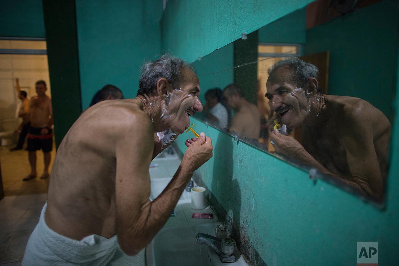 """A Cuban migrant shaves at the migrant shelter """"Casa del Migrante"""" in Nuevo Laredo, Tamaulipas state, Mexico, Saturday, March 25, 2017, across the border from Laredo, Texas. (AP Photo/Rodrigo Abd)"""