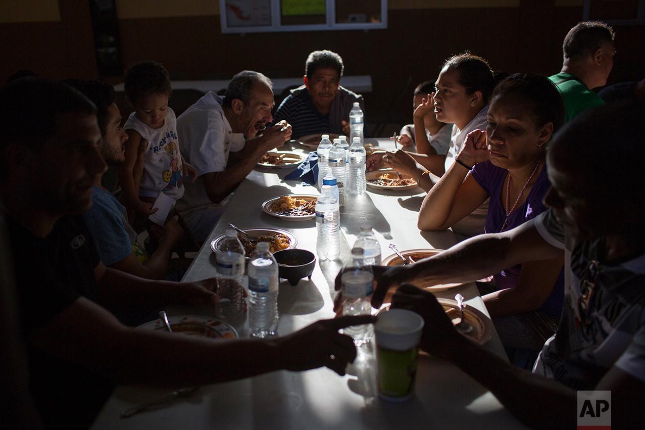 "Cubans eat dinner at the migrant shelter ""Casa del Migrante"" in Nuevo Laredo, Tamaulipas state, Mexico, Saturday, March 25, 2017, across the border from Laredo, Texas. (AP Photo/Rodrigo Abd)"