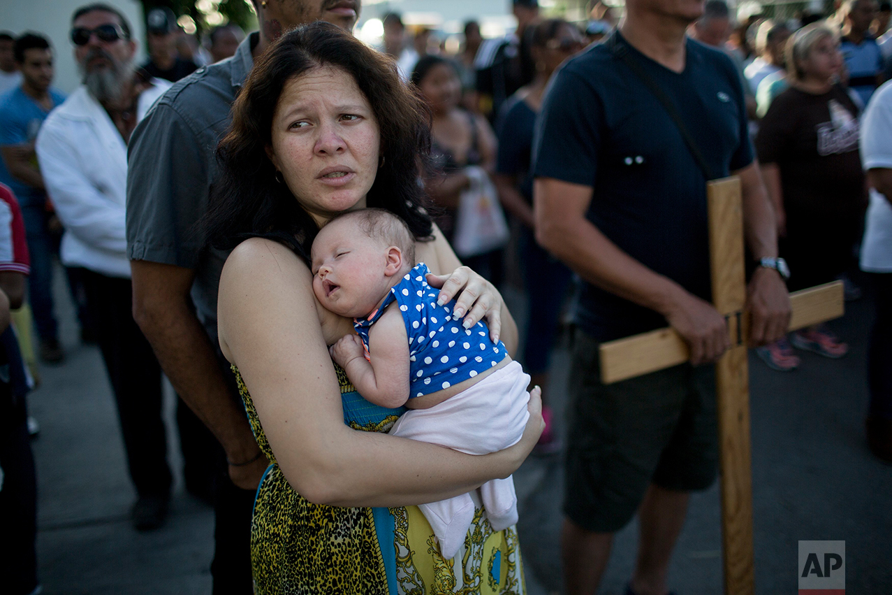 Cuban Elaide Vilchez carries her one-month-old daughter Emily Melania Garcia during a religious procession adapted to reflect the plight of immigrants, in Nuevo Laredo, Tamaulipas state, Mexico, Friday, March 24, 2017, across the border from Laredo, Texas. (AP Photo/Rodrigo Abd)