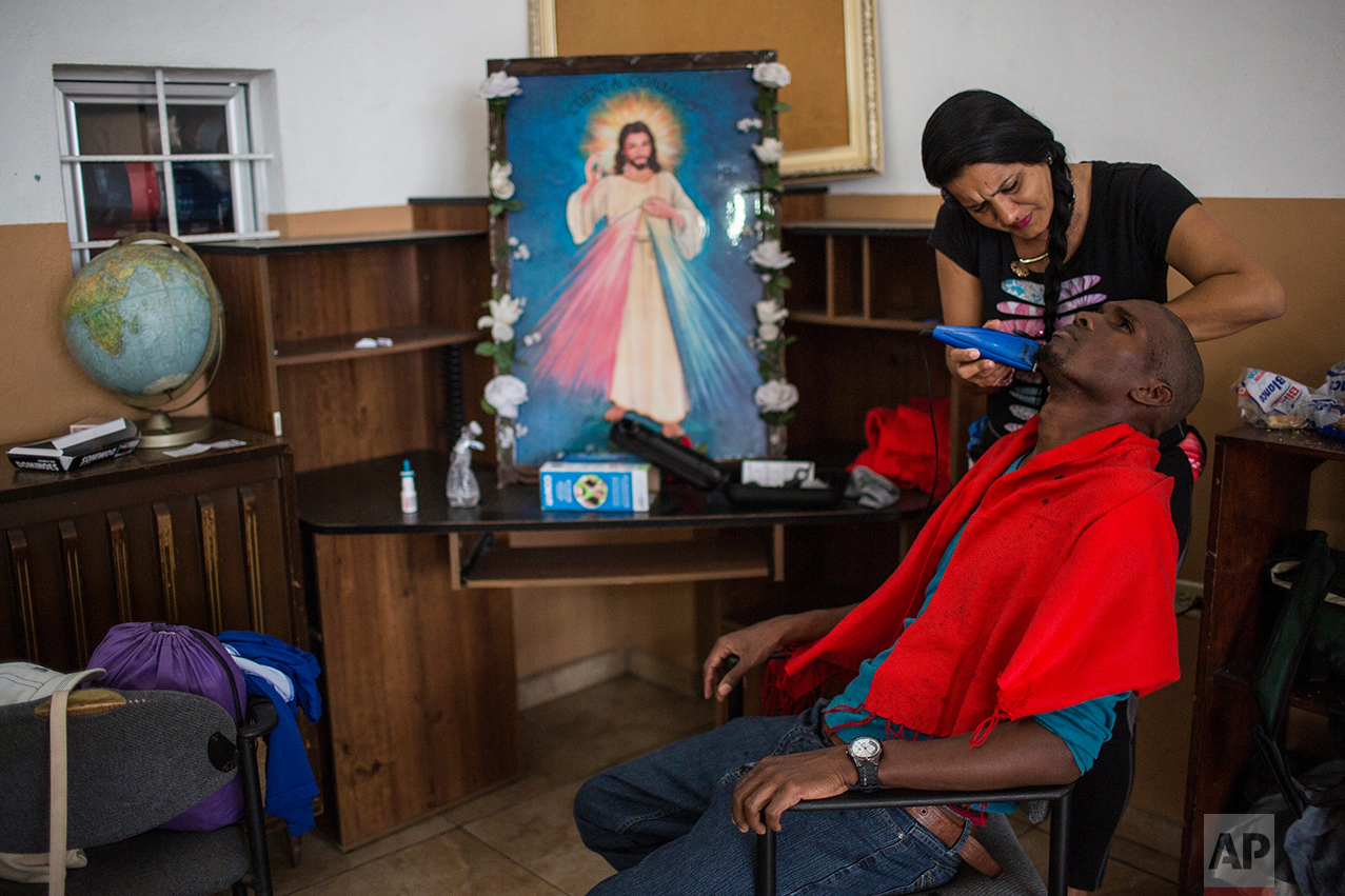 "A Cuban migrant shaves her husband's beard at the migrant shelter ""Casa del Migrante"" in Nuevo Laredo, Tamaulipas state, Mexico, Saturday, March 25, 2017, across the border from Laredo, Texas. (AP Photo/Rodrigo Abd)"