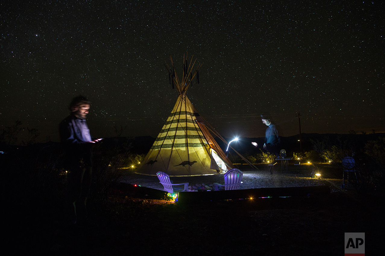 Associated Press team, writer Christopher Sherman, right, and photographer Rodrigo Abd, stand next to their tipi-style tent lodging at Tin Valley Retro Rentals in Terlingua, Texas, near the US-Mexico border, Monday, March 27, 2017. The AP has sent the team on a nearly two-week journey, from west to east along the entire length of the US-Mexico, to bring us fresh voices and images from both sides of these vast and varied borderlands and see what is happening on the ground. (AP Photo/Rodrigo Abd)