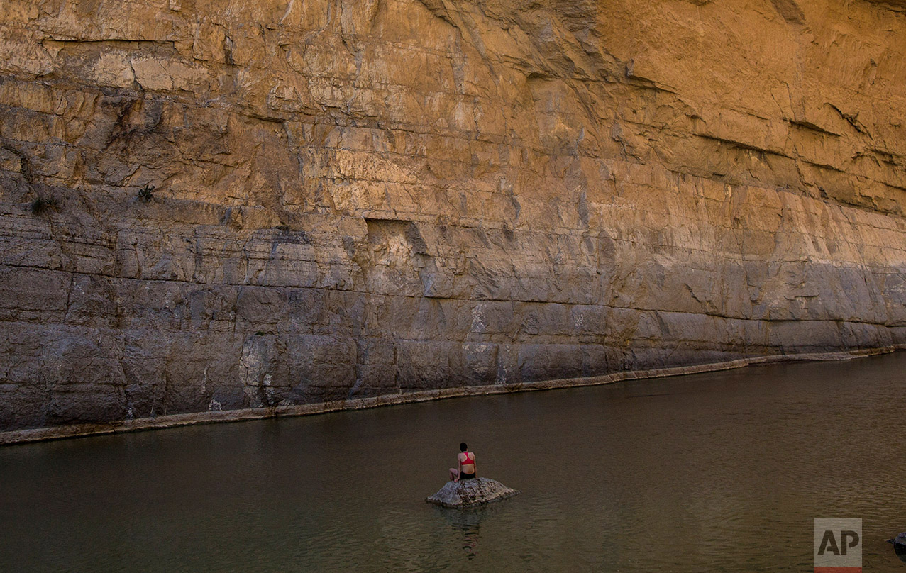 """Margaret McCall, a clean energy consultant from Chicago, sits in Santa Elena Canyon in the Rio Grande river just feet from a cliff face that is Mexico, facing her, as she vacations at Big Bend National Park in Texas, Monday, March 27, 2017. When asked about the border wall, McCall said: """"My first thought is: has Donald Trump seen this cliff? Because unless you're building a 500-foot wall it's really not going to cut it."""" (AP Photo/Rodrigo Abd)"""