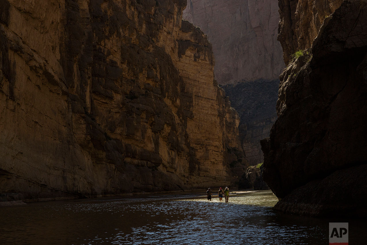 Tourists walk through Santa Elena Canyon, wading through the water of the Rio Grande, between Mexico, left, and the US, right, as they vacation at Big Bend National Park in Texas, Monday, March 27, 2017. (AP Photo/Rodrigo Abd)