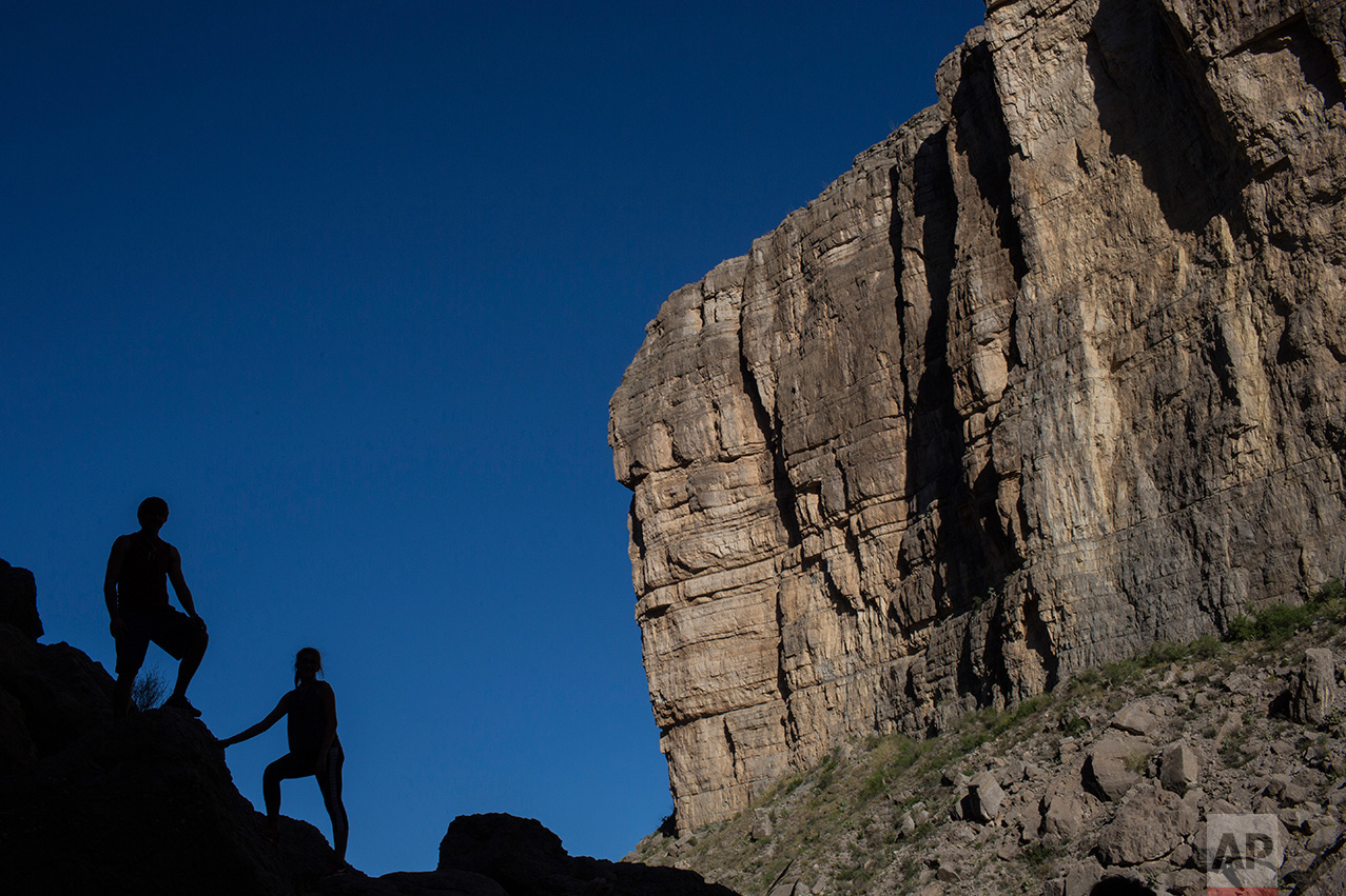Tourists pose for a family portrait in Santa Elena Canyon, just feet from a cliff face that is Mexico, on the banks of the Rio Grande river in Big Bend National Park in Texas, Monday, March 27, 2017. (AP Photo/Rodrigo Abd)