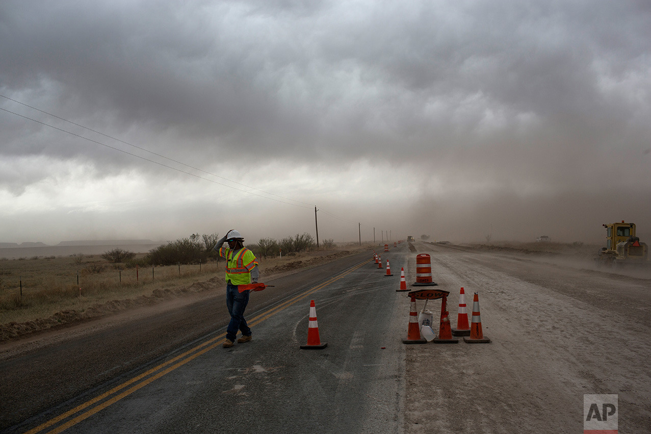 A road worker holds on to his hard hat during a dust storm near Valentine, Texas, about 20 miles from the US-Mexico border, Tuesday, March 28, 2017. (AP Photo/Rodrigo Abd)