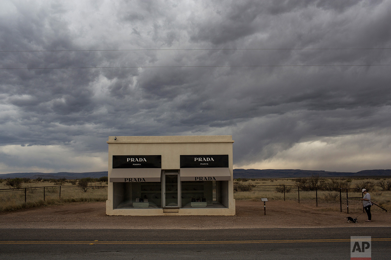A woman walks her dog next to an art installation made to look like a Prada retail store along a highway near Valentine, Texas, about 20 miles from the US-Mexico border, Tuesday, March 28, 2017. (AP Photo/Rodrigo Abd)
