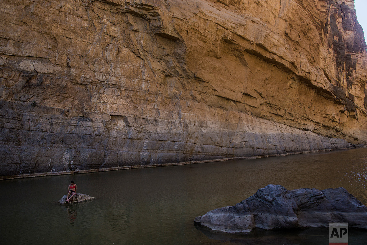 "Margaret McCall, a clean energy consultant from Chicago, sits on a rock in Santa Elena Canyon in the Rio Grande river just feet from a cliff face that is Mexico, behind her, as she vacations at Big Bend National Park in Texas, Monday, March 27, 2017. ""My first thought is: has Donald Trump seen this cliff?"" McCall said. ""Because unless you're building a 500-foot wall it's really not going to cut it."" (AP Photo/Rodrigo Abd)"