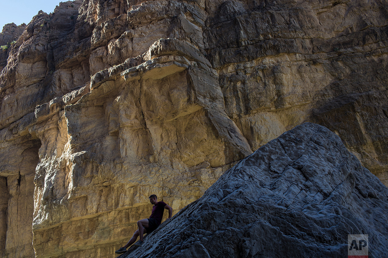 A man descends a rock on the bank of the Rio Grande river, just feet from a cliff face that is Mexico, in Santa Elena Canyon as he vacations at Big Bend National Park in Texas, Monday, March 27, 2017. (AP Photo/Rodrigo Abd)