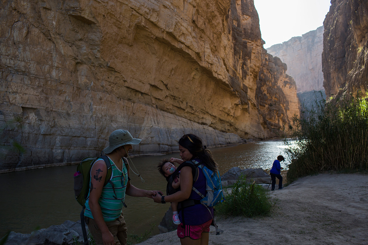 Tourists stand in Santa Elena Canyon, on the bank of the Rio Grande river, just feet from a cliff face that is Mexico, left, as they vacation at Big Bend National Park in Texas, Monday, March 27, 2017. (AP Photo/Rodrigo Abd)