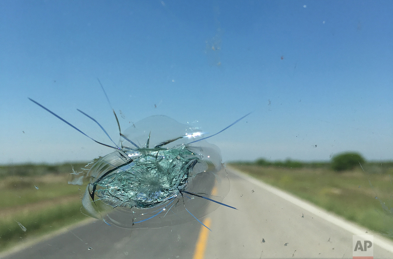 A stone broke the windshield near Piedras Negras, Mexico, Sunday, March 26, 2017, as the AP team drove about 12 hours along the US-Mexico border from The Rio Grand Valley to Terlingua, Texas. The incident delayed them by about two hours as they argued with the insurance company that didn't want to cover the crack, but an adjuster came out and they'll have it fixed somewhere further along the route. It wasn't going to happen on a Sunday in Piedras Negras, MÈxico. (AP Photo/Christopher Sherman)