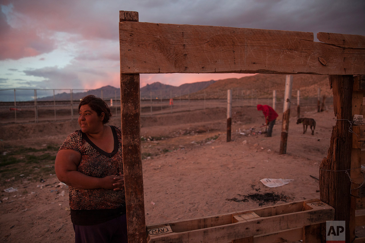 A woman stands outside her home located next to the border fence between the U.S. and Mexico, the gray, metal gate behind her, in the Anapra neighborhood of Ciudad Juarez, Mexico, Wednesday, March 29, 2017, across the border from Sunland Park, New Mexico. This week, Mexican residents like her are losing their view toward the U.S. as each hour a crew welds into place two more segments of steel border fence. (AP Photo/Rodrigo Abd)