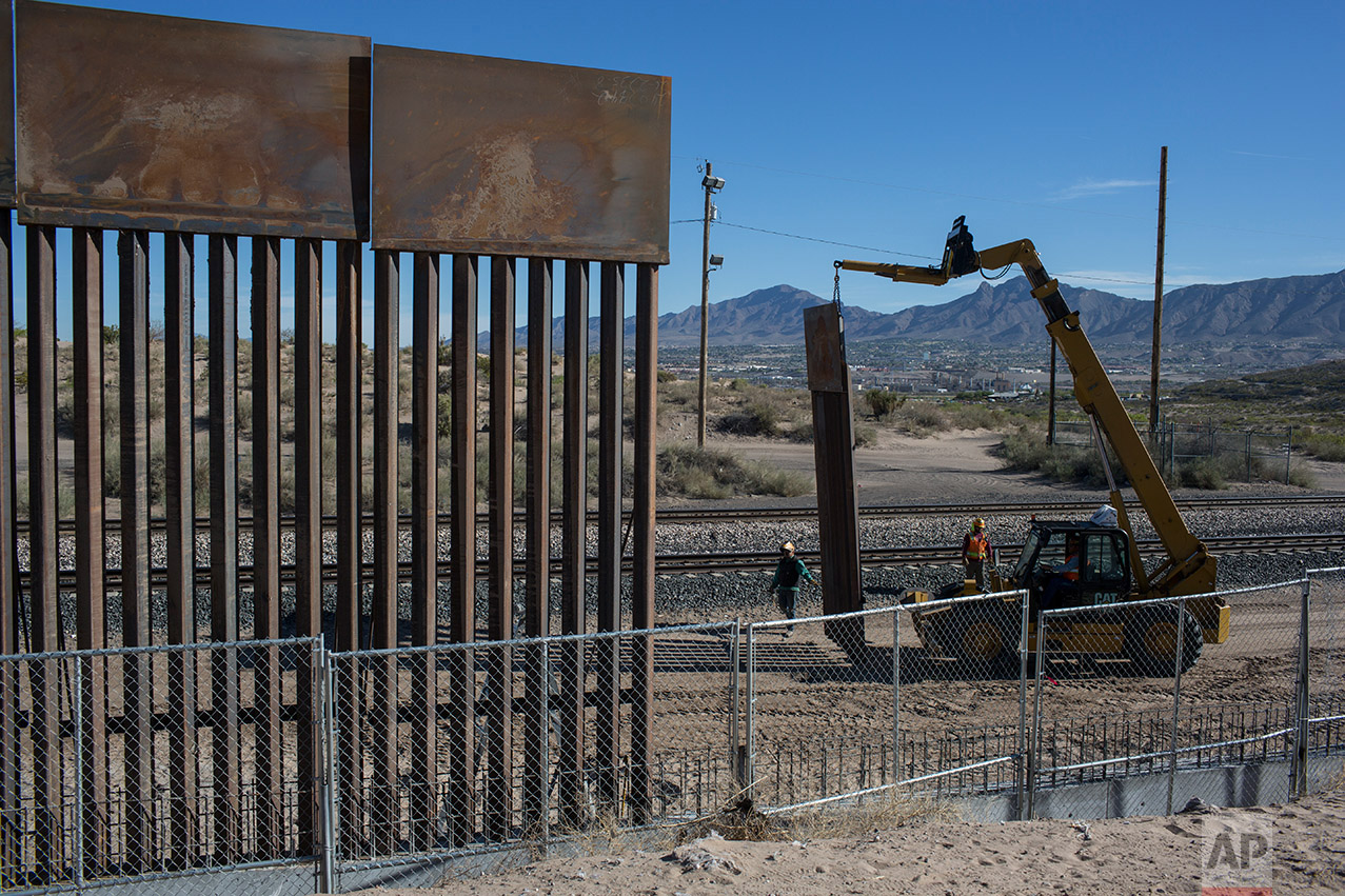 Workers use a crane to lift a segment of a new fence into place on the U.S. side of the border with Mexico, where Sunland Park, New Mexico, meets the Anapra neighborhood of Ciudad Juarez, Mexico, Thursday, March 30, 2017. Residents on the Mexico side estimate 15 to 20 panels go up daily. (AP Photo/Rodrigo Abd)