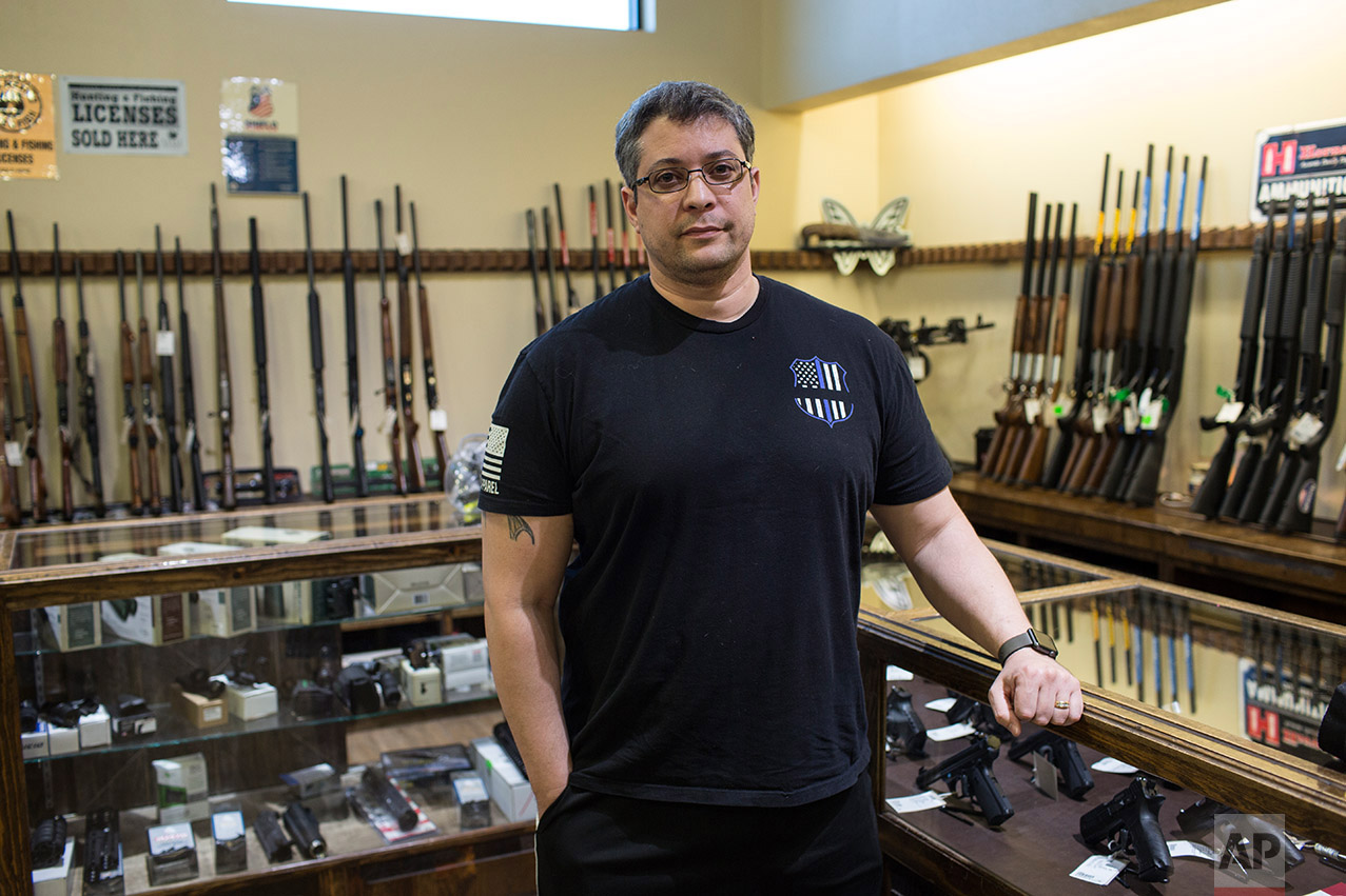 Randy Calderon poses for a photo in the, Sportman's Elite gun shop in El Paso, Texas, Thursday, March 30, 2017. (AP Photo/Rodrigo Abd)